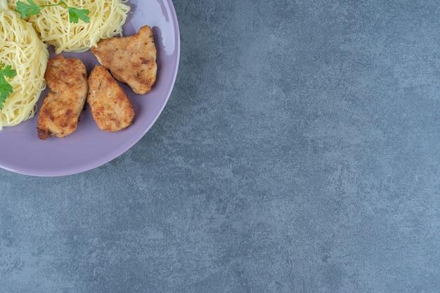 Ali di pollo alla griglia e spaghetti sul piatto viola.