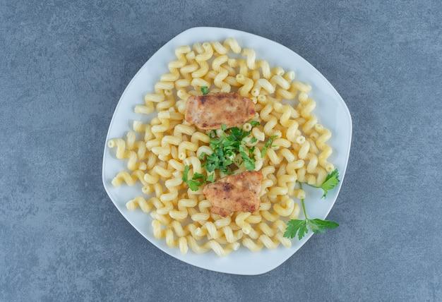 Alette di pollo grigliate su pasta bollita.