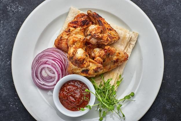 Жареные куриные крылышки с соусом барбекю, лаваш, микрогрин и луковые кольца, на белой тарелке, на темном столе. вид сверху