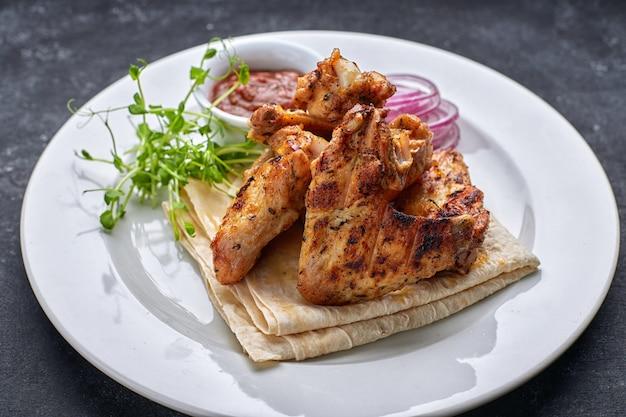 Жареные куриные крылышки с соусом для барбекю, лаваш, микрогрин и луковые кольца, на белой тарелке, на темном столе