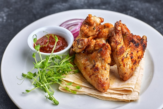 Grilled chicken wings with barbecue sauce, pita bread, microgreen and onion rings, on a white plate, against a dark table