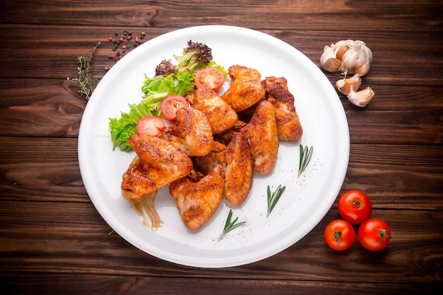 Grilled chicken wings with vegatables and seasoning on a wooden background