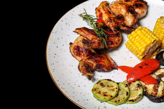Grilled chicken wings with vegetables on black