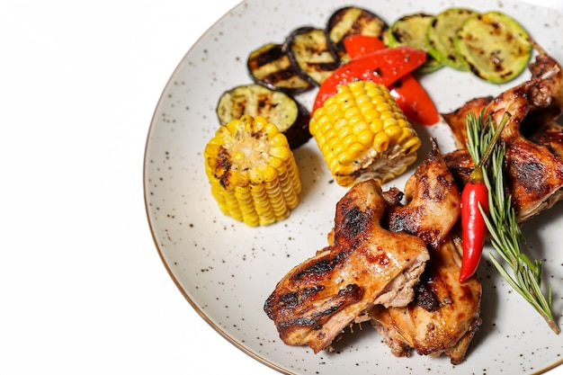 Grilled chicken wings with vegetables on white