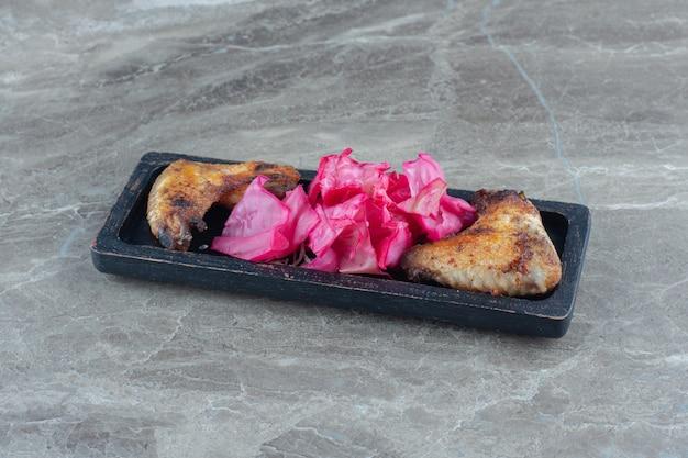 Pollo alla griglia con sottaceti di cavolo nero su tavola di legno