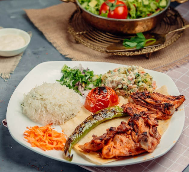 Grilled chicken with salad, rice, tomato and green chili.