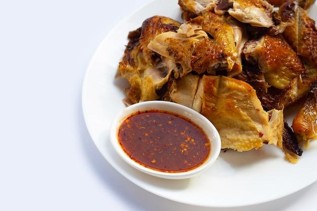 Курица-гриль с острым соусом на белой поверхности