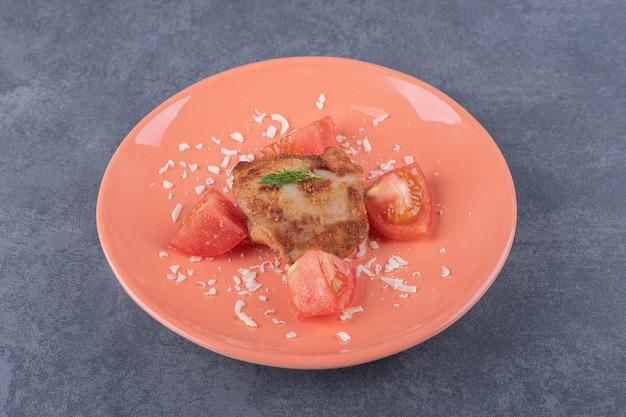 Курица-гриль с ломтиками помидора на оранжевой тарелке.
