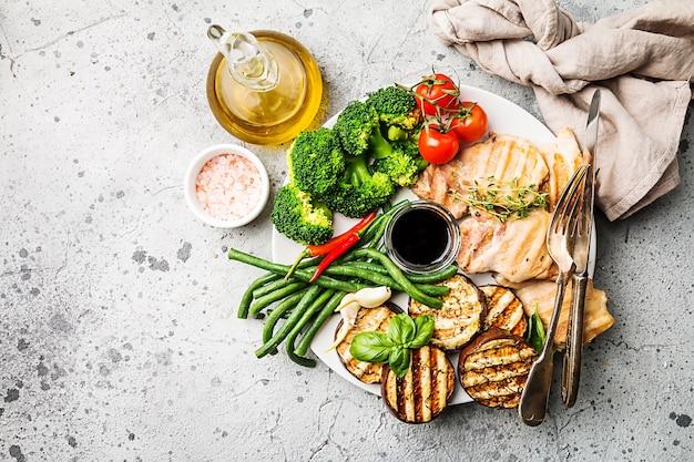 Курица-гриль с овощами на тарелке над серым