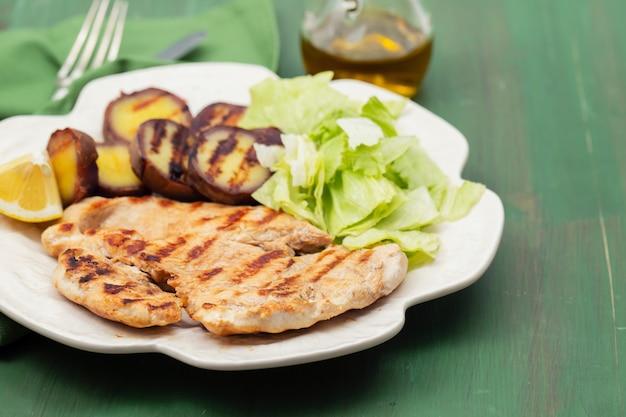 흰 접시에 야채와 닭고기 구이