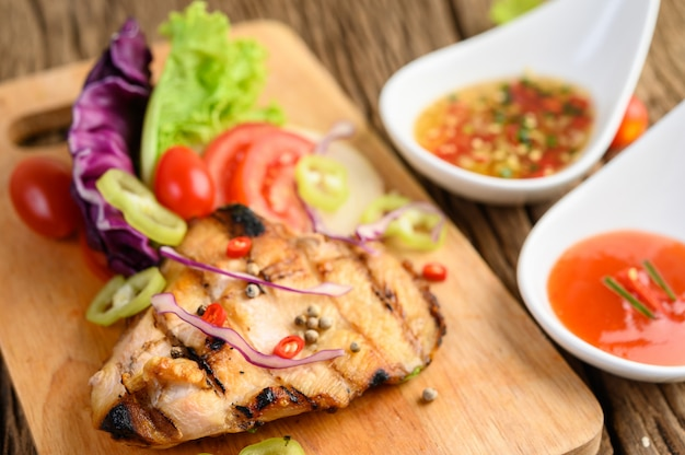 Grilled chicken on a wood cutting board with salad, tomatoes, chilies cut into pieces, and sauce.