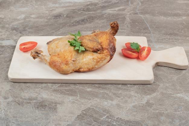 Pollo alla griglia su tavola di legno con fette di pomodoro.