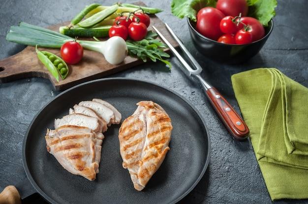 Филе курицы гриль на сковороде. сырые овощи в миске, кухонном фоне. выборочный фокус