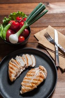 Филе курицы гриль на сковороде. сырые овощи в миске, деревянный фон