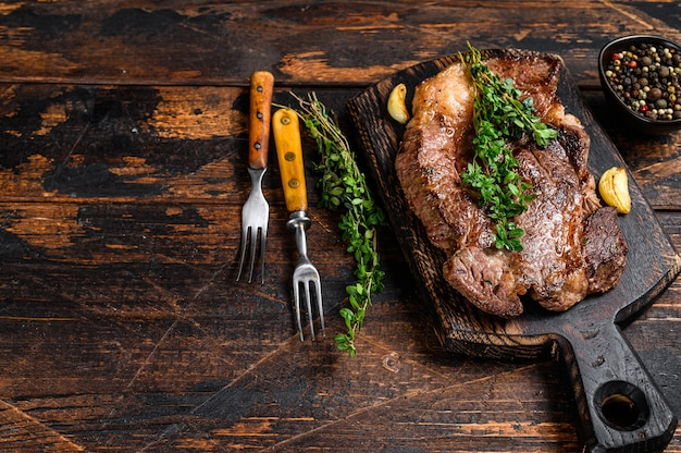 Grilled chuck eye roll beef meat steak on a cutting board