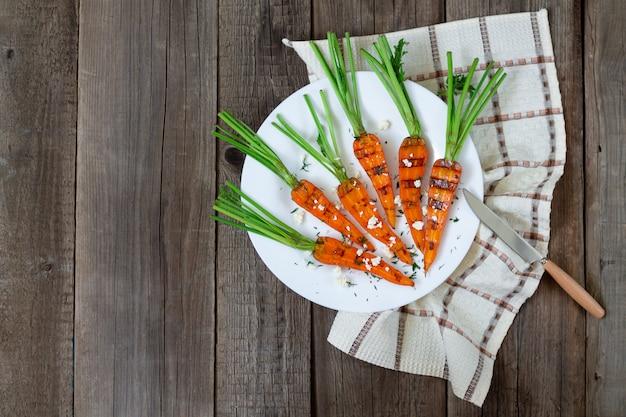ビューの上から素朴な木製のテーブルできれいな有機ニンジンをグリル。健康的な食事のコンセプト