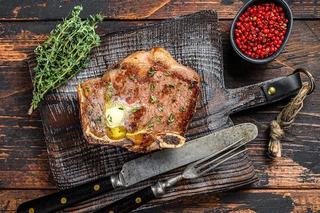 骨付きのクラブビーフステーキまたはサーロインのグリル。ダークウッドのテーブル。上面図。