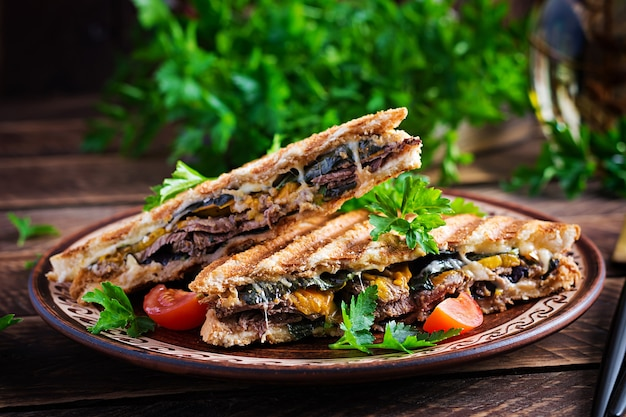 Клубный сэндвич-панини на гриле с говядиной, помидорами, сыром и листовой горчицей. вкусный завтрак или перекус.