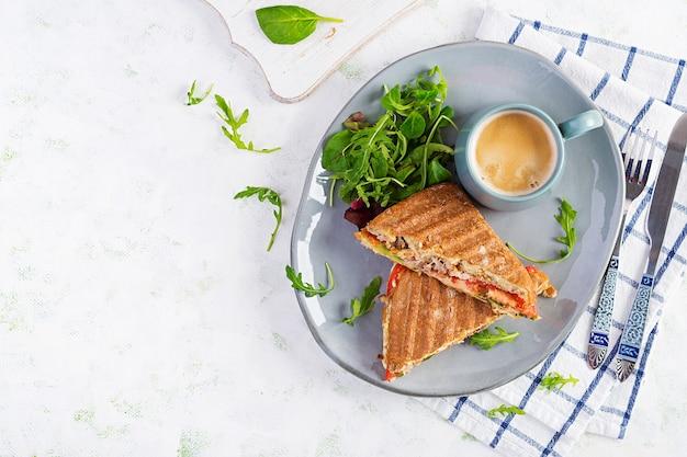 Клубный сэндвич-панини на гриле с говядиной, помидорами, сыром, листьями салата и чашкой кофе