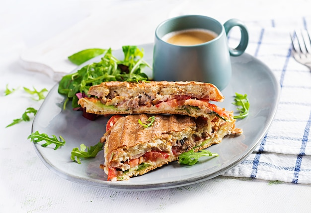 Grilled club sandwich panini with beef, tomato, cheese, lettuce and cup of coffee