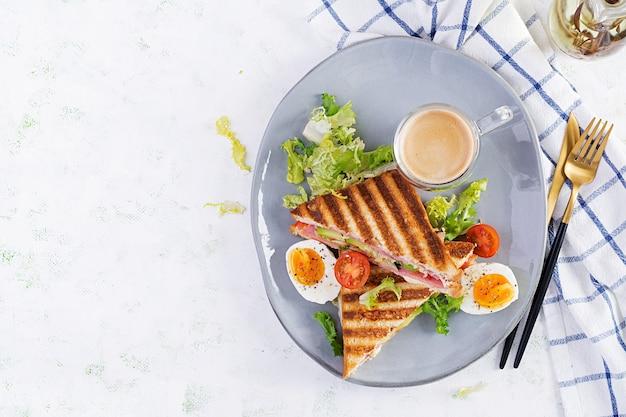 Клубный сэндвич-панини на гриле с ветчиной, помидорами, сыром, авокадо и чашкой кофе