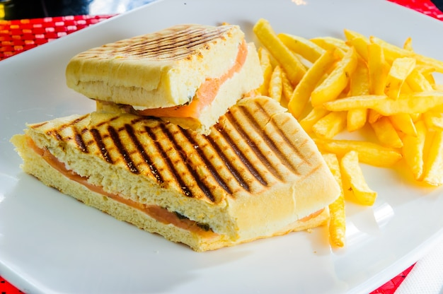 Grilled club sandwich with french fries isolated on white plate.