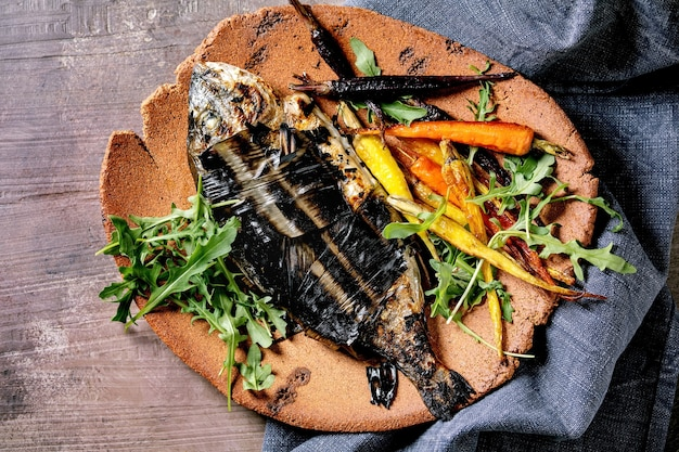 Grilled cooked fresh gutted sea bream or dorado fish on ceramic plate wrapped in bamboo leaves served with herbs, colorful carrots, blue napkin over dark brown  surface. top view, flat lay