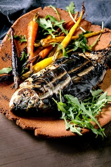 Grilled cooked fresh gutted sea bream or dorado fish on ceramic plate wrapped in bamboo leaves served with herbs, colorful carrots, blue napkin over dark brown texture surface. close up