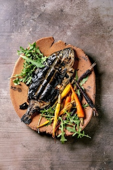 Grilled cooked fresh gutted sea bream or dorado fish on ceramic plate wrapped in bamboo leaves served with herbs, colorful carrots over dark brown texture surface. top view, flat lay