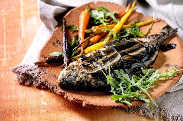 Grilled cooked fresh gutted sea bream or dorado fish on ceramic plate wrapped in bamboo leaves served with herbs, colorful carrots, white napkin over orange metal surface. close up