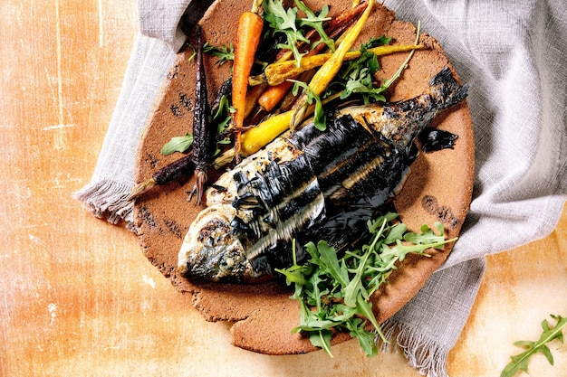 Grilled cooked fresh gutted sea bream or dorado fish on ceramic plate wrapped in bamboo leaves served with herbs, colorful carrots, white napkin over orange metal surface. top view, flat lay