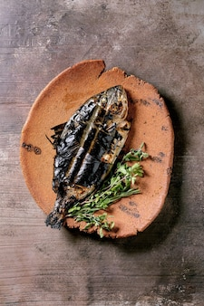 Grilled cooked fresh gutted sea bream or dorado fish on ceramic plate wrapped in bamboo leaves served with herbs over dark brown  surface. top view, flat lay