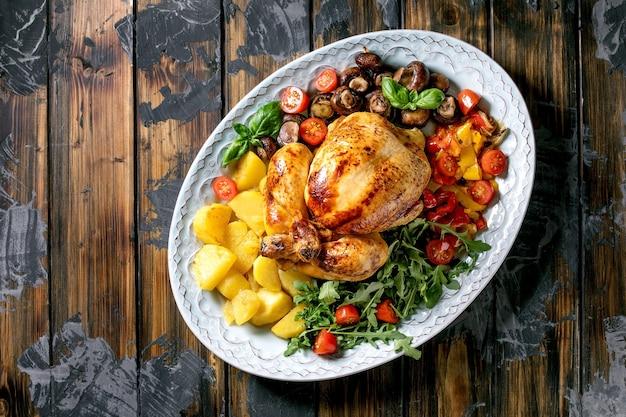 구운 피망, 양파, 구운 감자, 체리 토마토, 버섯 및 허브를 어두운 나무 표면 위에 세라믹 접시에 야채 장식과 함께 구운 전체 닭고기. 평면도, 평면 위치