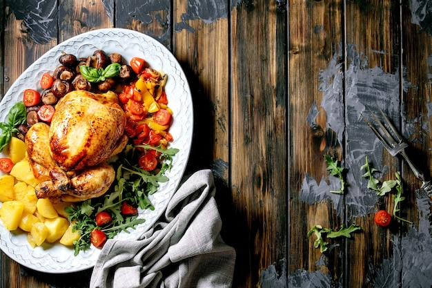 구운 피망, 양파, 구운 감자, 체리 토마토, 버섯, 허브를 어두운 나무 표면 위에 세라믹 접시에 야채 장식으로 구운 전체 닭고기. 평평하다. 공간 복사