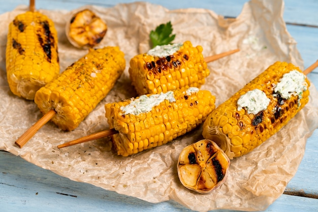 Grilled corn on a blue wooden table with green sauce