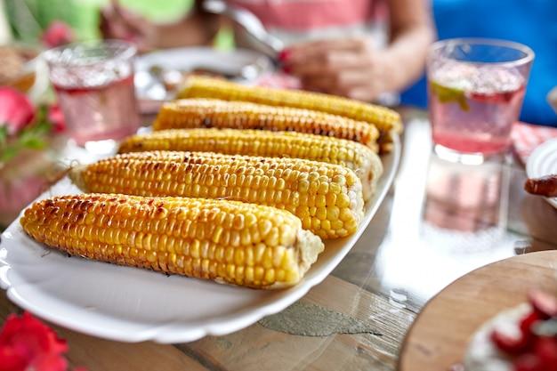 Жареные кукурузные початки на тарелке на обеденном столе, разнообразные закуски, сервированные на столе на открытом воздухе.