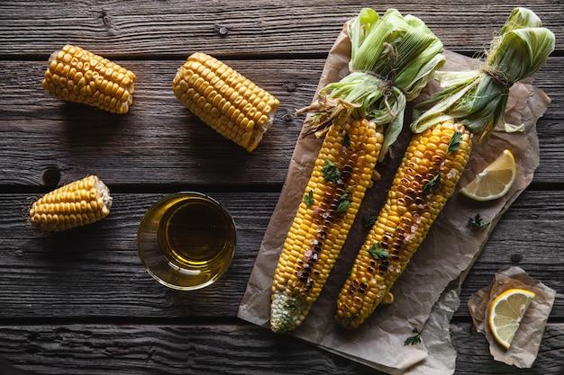 Жареные кукурузные початки с соусом, кориандром на старых деревянных фоне. мексиканская еда. вид сверху. копирование пространства, здоровое питание, овощи