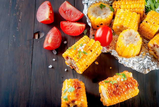 Grilled corn cobs with solt, spices and tomatoes