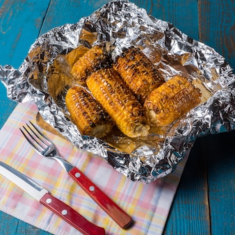 Grilled corn on a foil over old blue wooden table