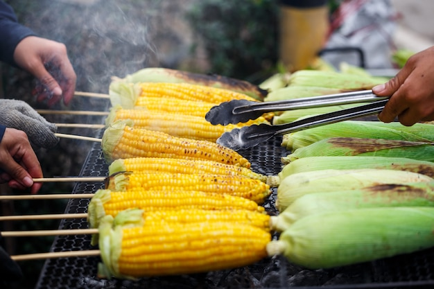 Grilled corn on the grill , cooking several fresh yellow brown golden corn