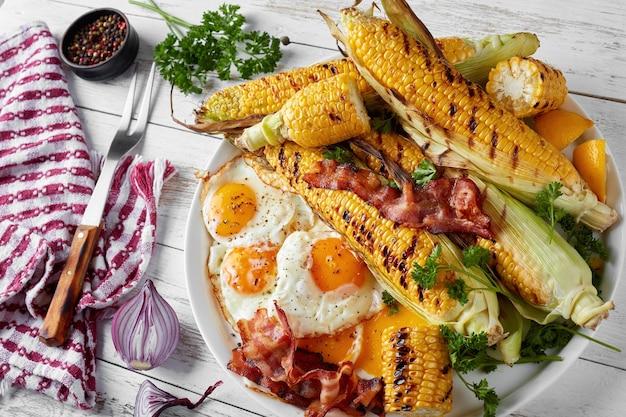 ナプキンとフォークの古い素朴なテーブルの上の白い皿の上に目玉焼きとベーコンのスライスとトウモロコシの穂軸のグリル、上からの水平方向のビュー、クローズアップ