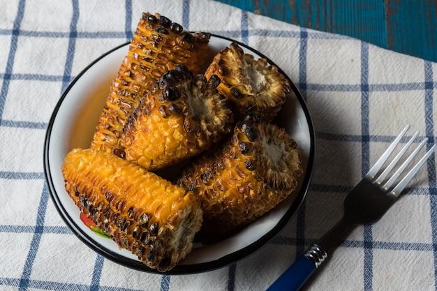古い青い木製のテーブルの上皿に焼きトウモロコシ。
