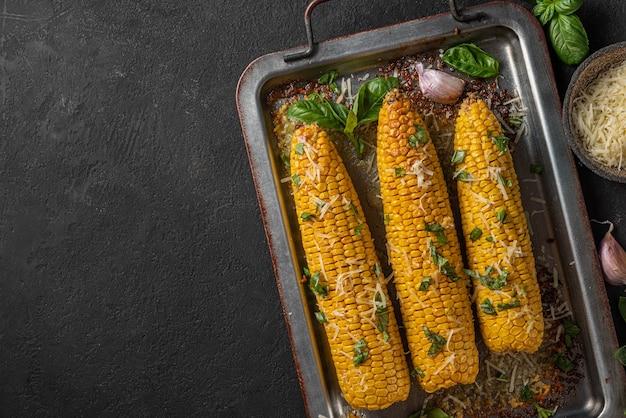 Кукуруза на гриле в початках с маслом, пармезаном и базиликом на противне на черном фоне. вид сверху с копией пространства. здоровая вегетарианская еда