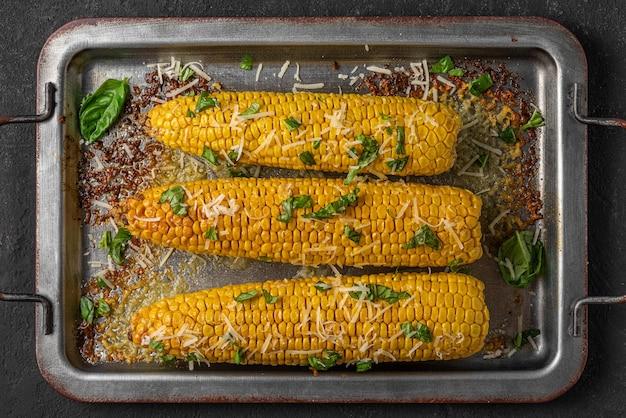 Кукуруза на гриле в початках с маслом, пармезаном и базиликом на противне. вид сверху