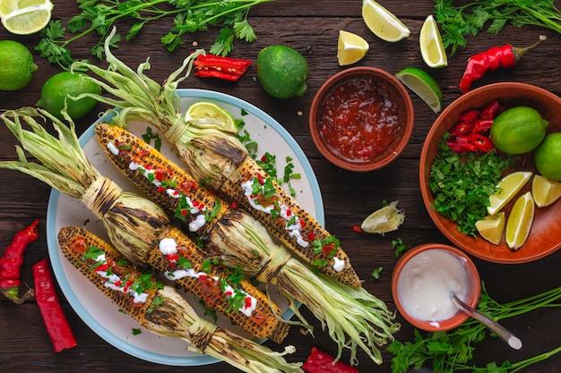 トウモロコシのグリルとハーブとソース。伝統的なメキシコ料理とラテンアメリカ料理