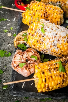 Grilled corn with a sprinkle of cheese, hot chili pepper and lemon on a dark stone table.