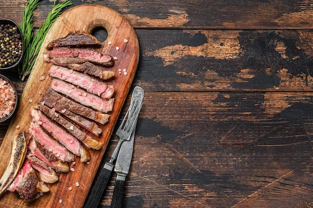 Ковбойский стейк из говядины или рибай с зеленью и специями. вид сверху. скопируйте пространство.