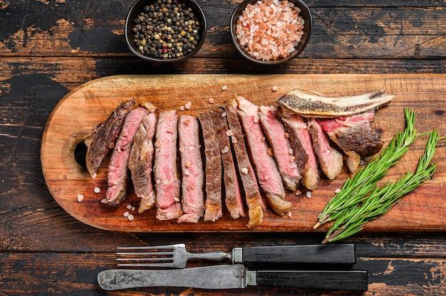 Ковбойский стейк из говядины или рибай с зеленью и специями. деревянная темная поверхность. вид сверху.