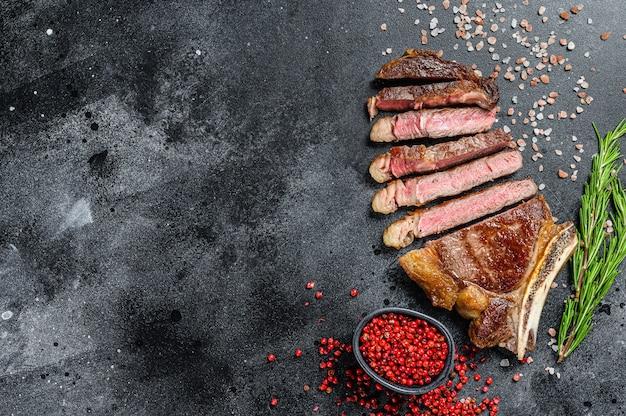 Ковбойский стейк из говядины на гриле или рибай с травами и специями. вид сверху. скопируйте пространство.