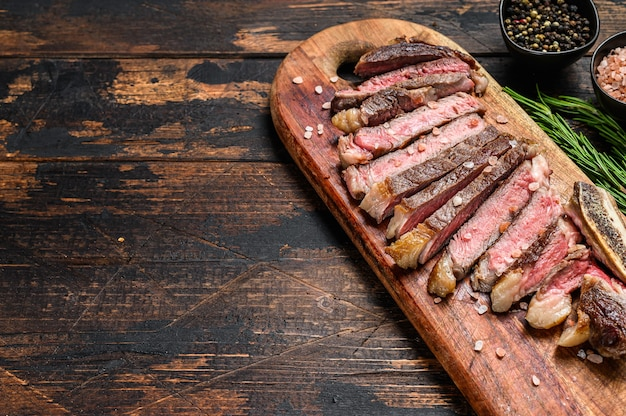 Grilled cowboy or rib eye beef steak with herbs and spices.